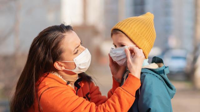 Un mère venant en aide à son enfant pour mettre son masque covid19